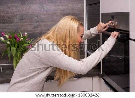 Woman press the oven's button in modern kitchen - stock photo