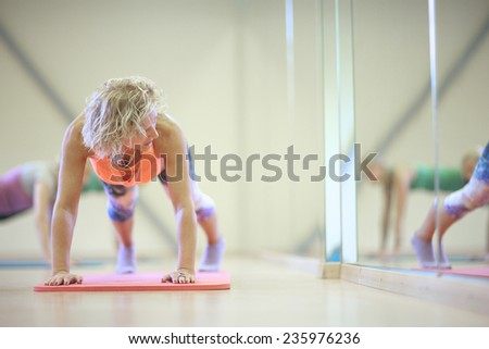 Woman press ups next to the mirror in gym - stock photo