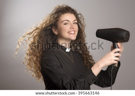 Woman priest with long hair using a hair dryer