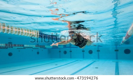 Woman professional swimmer wearing black swimsuit inside swimming pool.