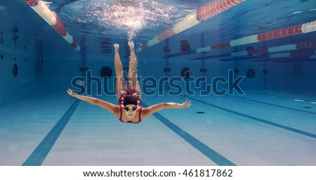 Woman professional swimmer wearing red swimsuit inside swimming pool.