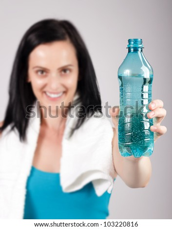 Woman promoting water while smiling - stock photo