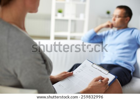 Woman psychologist filling in card of her patient - stock photo
