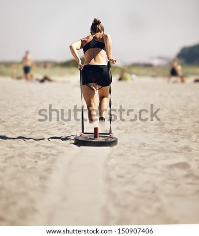 Woman Pulling Crossfit Sled - stock photo