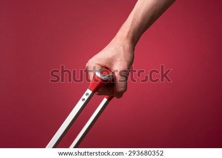 Woman pulling luggage by the handle. Photographed in front of a red backdrop with studio lighting.
