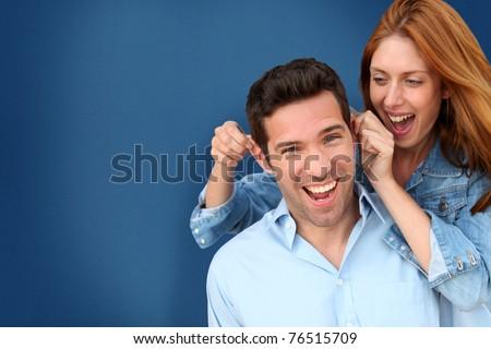 Woman pulling on her boyfriend's ears - stock photo