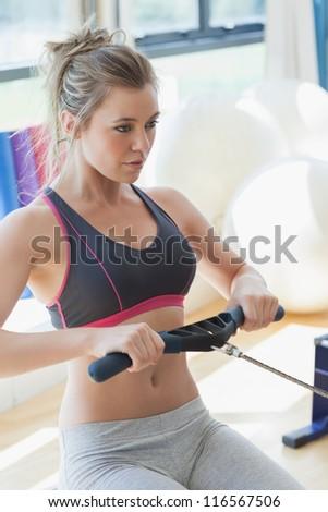 Woman pulling on row machine in fitness studio - stock photo