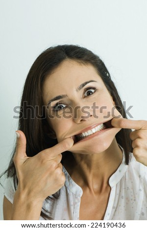 Woman pulling sides of mouth, looking at camera, portrait - stock photo