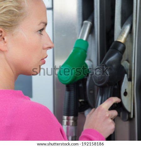 Woman pumping gasoline fuel in car at gas station. Petrol or gasoline being pumped into a motor vehicle car. - stock photo