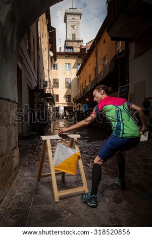 Woman punching at control point, taking part in city race in old european city. File contains clipping path of woman. - stock photo