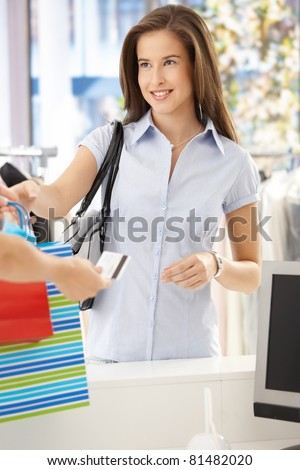 Woman purchasing clothes in shop, getting back credit card, smiling at shop assistant.? - stock photo