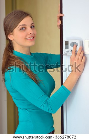 woman push button digital thermostat at house - stock photo