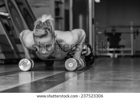 Woman push-ups on the floor.Gym woman push-up strength pushup exercise with dumbbell in a fitness workout. Athletic young woman doing exercises on the floor is pushed. - stock photo