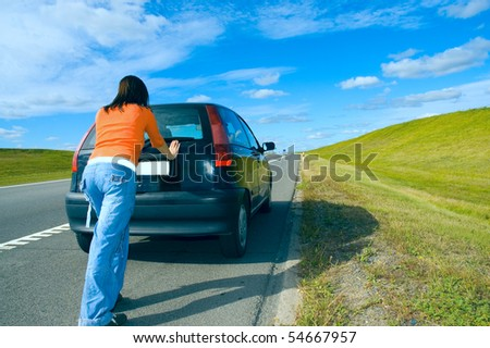 woman pushing a car - stock photo