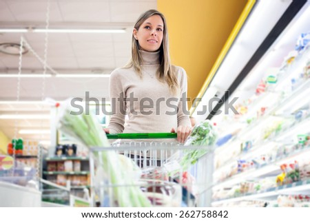 Woman pushing a shopping cart in a grocery store - stock photo