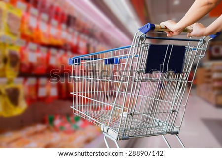 woman pushing empty shopping cart in supermarket