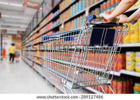 woman pushing empty shopping cart in supermarket - stock photo
