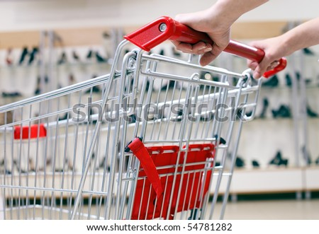Woman pushing shopping cart in shoe store, close-up