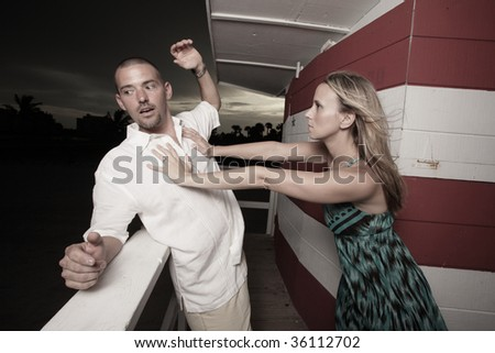 Woman pushing the man off the ledge