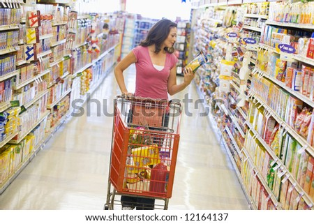 Woman pushing trolley along supermarket grocery aisle