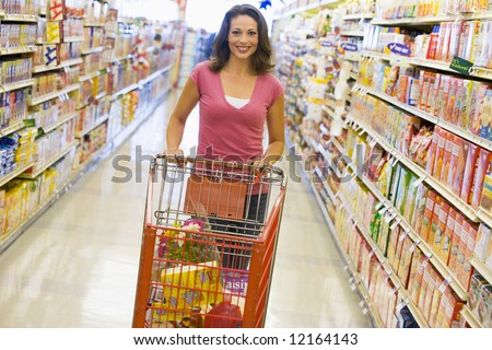 Woman pushing trolley along supermarket grocery aisle - stock photo