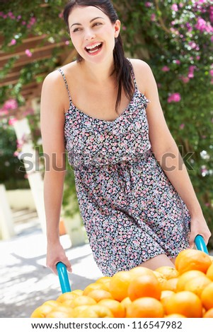 Woman Pushing Wheelbarrow Filled With Oranges - stock photo