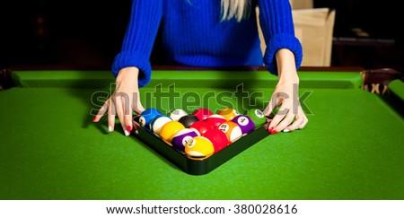 Woman puts a pyramid of balls for a pool on a billiard table. Billiard sport concept art. American pool billiard. Pool billiard game. - stock photo