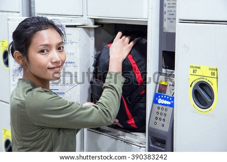 Woman puts backpack to safety locker
