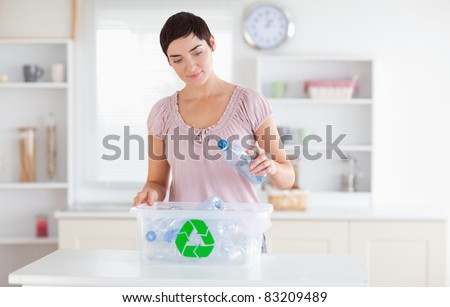 Woman putting bottles in a recycling box in a kitchen