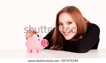 woman putting coin in piggy bank, white background - stock photo