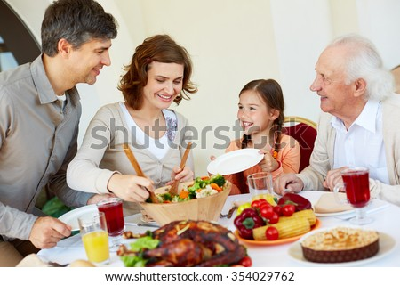 Woman putting cooked vegs on plate of little girl - stock photo