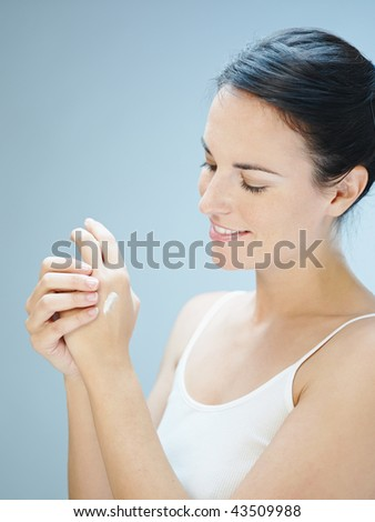 Woman putting cream on hands. Copy space - stock photo