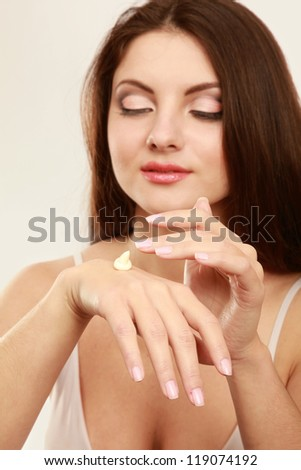 woman putting cream on her hands. Isolated on white background
