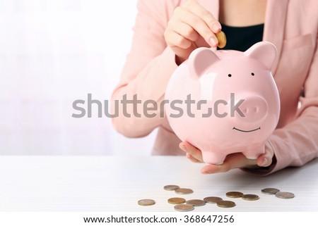 Woman putting euro coin into a piggy bank on the table. Financial savings concept - stock photo