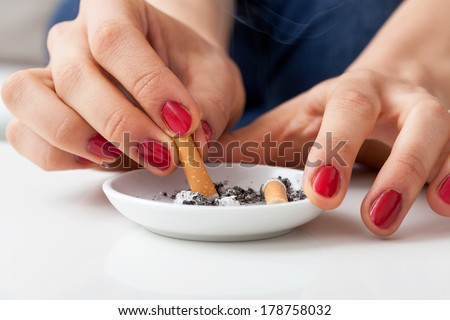Woman putting finished cigarette in an ashtray - stock photo