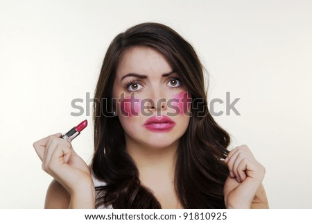 woman putting make up on and it when a bit to far so she looks silly