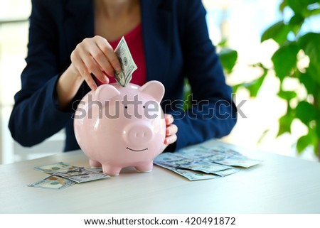 Woman putting money in piggy bank