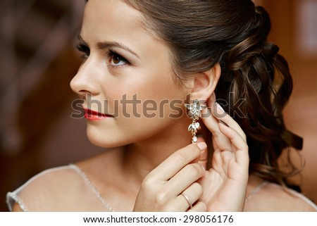 Woman putting on diamond earrings. Caucasian beauty lady trying and shopping jewelry.  - stock photo