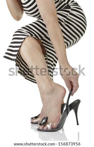Woman putting on heels over white background - stock photo