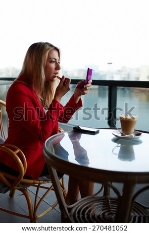 Woman putting on her lip gloss looking at the mirror while sitting in the coffee shop, young businesswoman applying make up during her work break at cafe, elegant woman smarten up before a date - stock photo