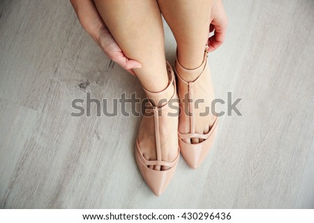 Woman putting on high heel shoes, top view