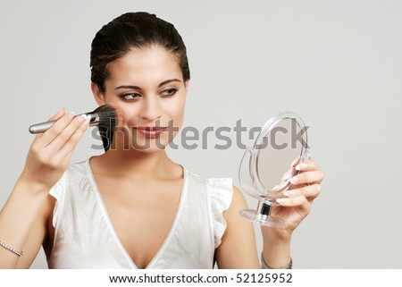 woman putting on makeup with blush brush - stock photo