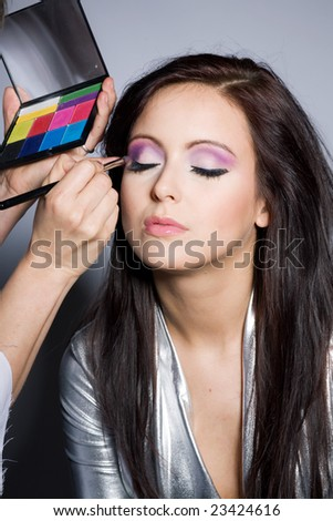 Woman putting on models eye make up