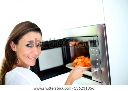 Woman putting plate in microwave oven - stock photo