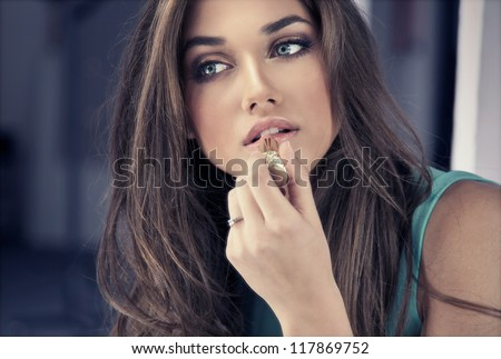 Woman putting red lipstick looking in mirror. - stock photo