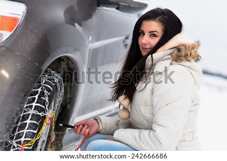 Woman putting winter tire chains on car wheel snow breakdown  - stock photo