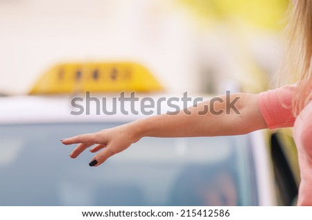 woman raising her arm to call a taxi - stock photo