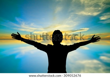 Woman raising her arms on sunset