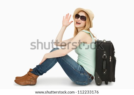 Woman raising her hand while sitting next to a suitcase against white background - stock photo