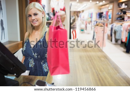 Woman  reaching  bag behind the counter and smiling - stock photo